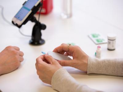 A close-up of two women's hands as they conduct a usability test of a digital app-enanced glucose testing device