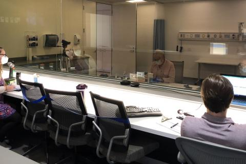 Two human factors researchers wearing surgical masks observe a human factors study of a medical device occurring in an observation room.