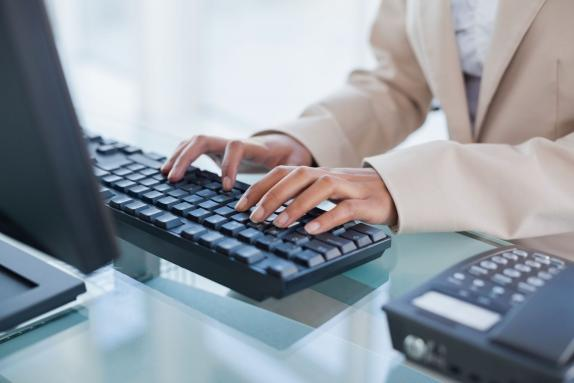 A woman's hands typing on a computer keyboard
